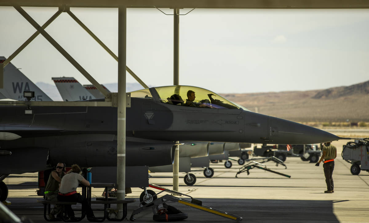 A pilot sits in the cockpit as another jet is ready for action as Nellis Air Force Base hosts a ...