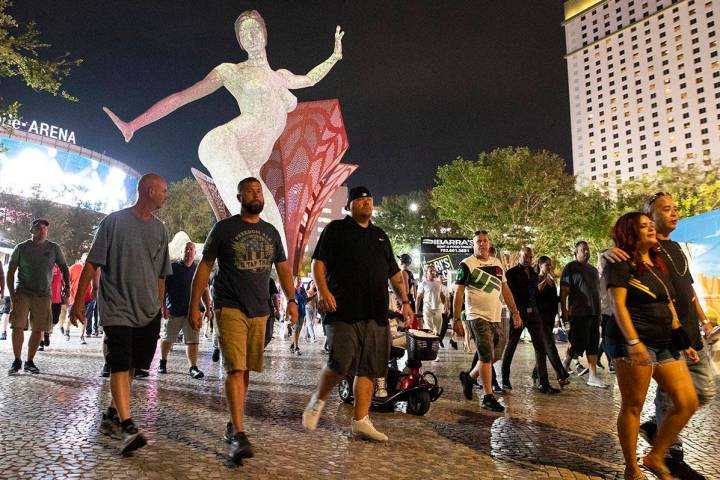 People, nearly all without masks, walk near T-Mobile Arena, on Saturday, July 10, 2021, in Las ...