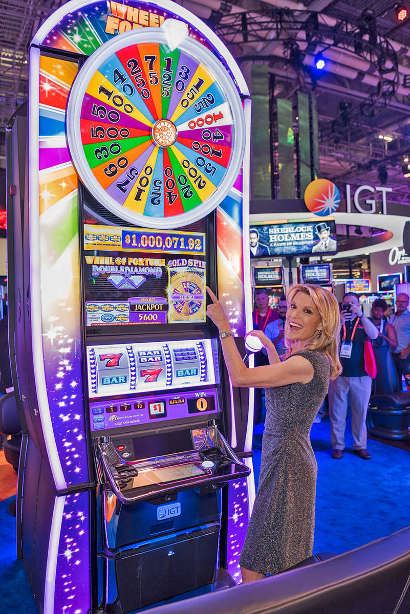 Wheel of Fortune co-host and letter-turner Vanna White plays a Wheel of Fortune slot machine at ...
