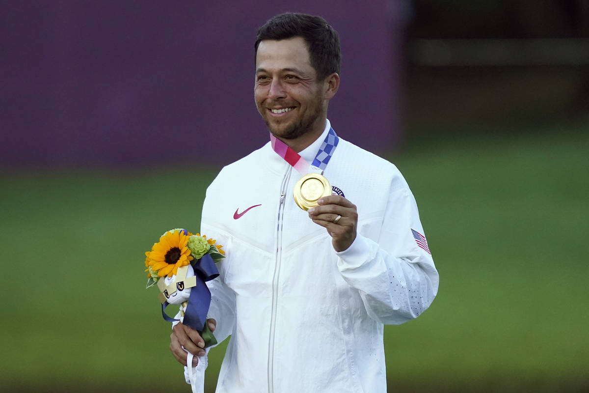 Xander Schauffele, of the United States, holds his gold medal after winning the men's golf even ...