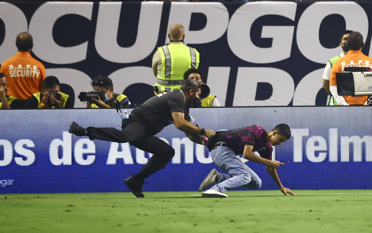 A security guard chases down a soccer fan during the second half of the Concacaf Gold Cup final ...
