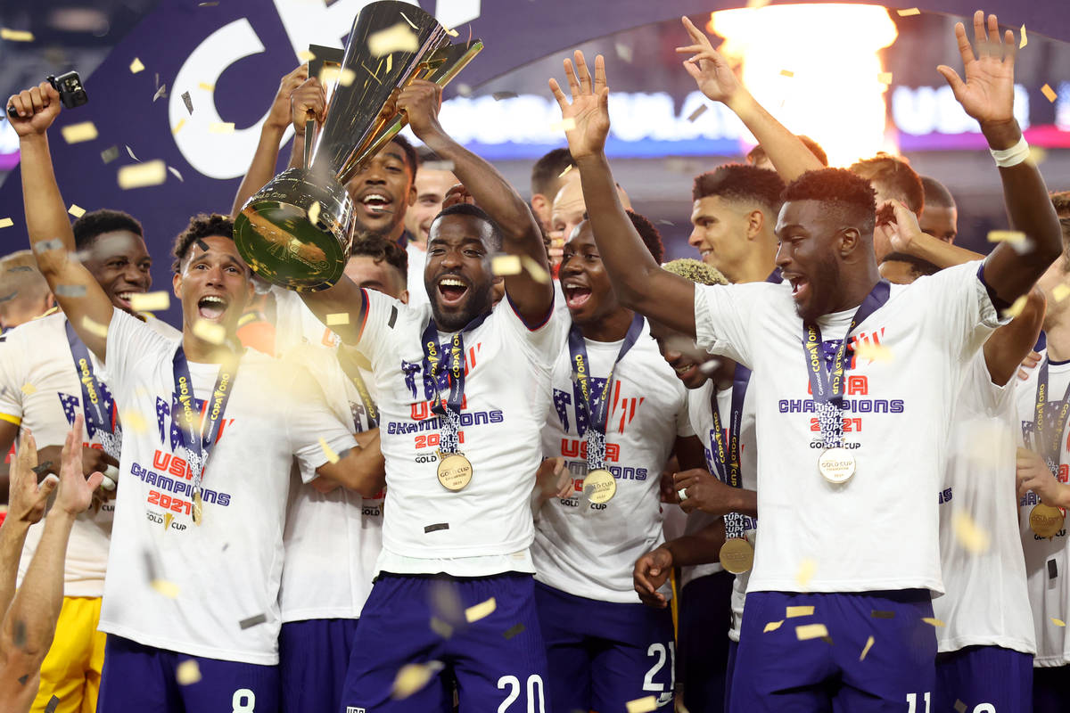 United States defender Shaq Moore (20) raises the trophy after his team's victory in the Concac ...