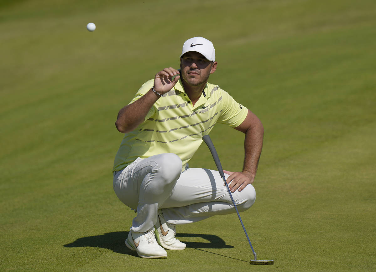 United States' Brooks Koepka catches his ball after it was cleaned by his caddie on the 18th gr ...