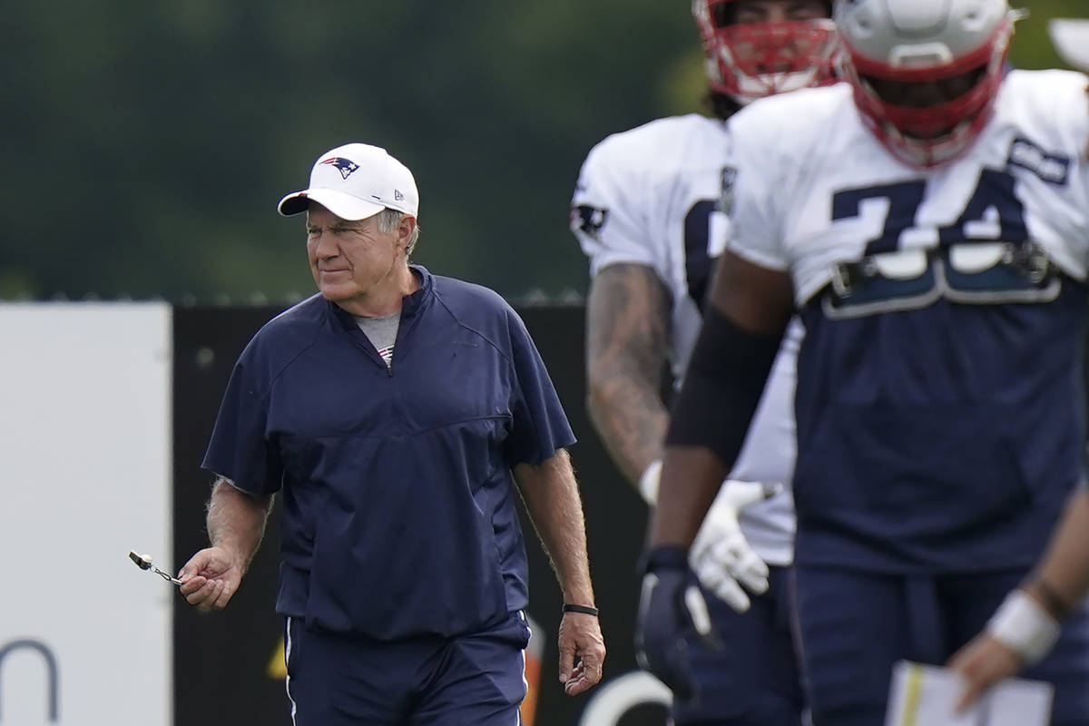 New England Patriots head coach Bill Belichick, left, walks on the field near players during an ...