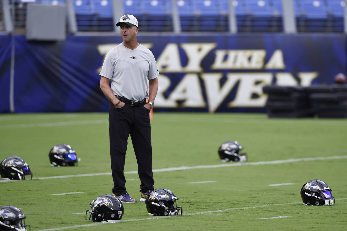 Baltimore Ravens coach John Harbaugh stands on the field before practice at NFL football traini ...