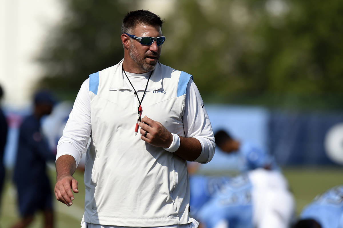 Tennessee Titans head coach Mike Vrabel watches his team warm up during NFL football training c ...