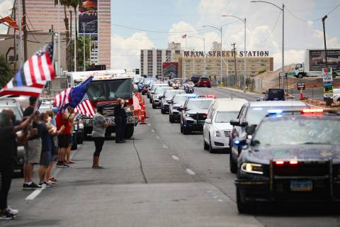 Bystanders watch a procession moving the body of slain Nevada Highway Patrol Trooper Micah May ...