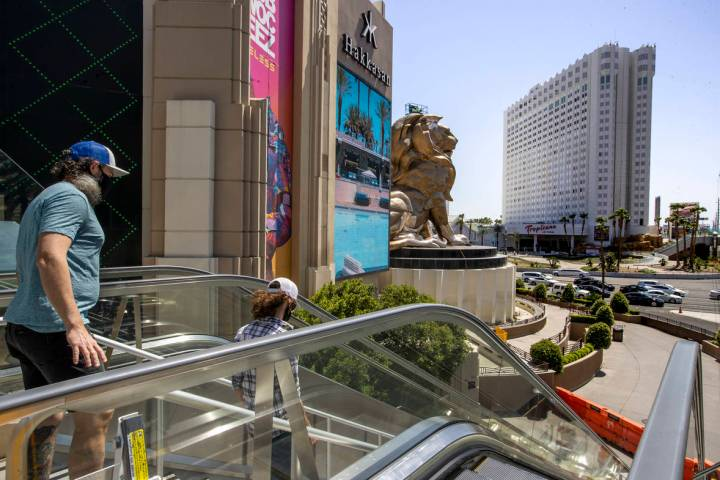 Pedestrians walk down stairs outside the MGM Grand across from the Tropicana on the Las Vegas S ...