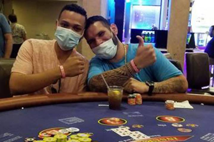 Brian Rodriguez, left, celebrates with a friend after hitting a jackpot at Bally's. (Caesars En ...