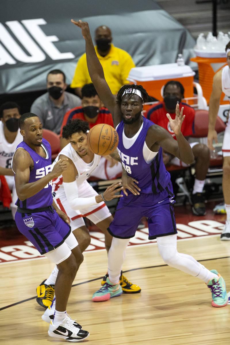 Sacramento Kings guard Matt Coleman, left, and center Neemias Queta, right, eye the ball as Was ...
