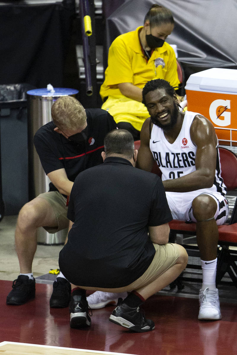Portland Trail Blazers forward Kenneth Faried (50) is attended to by trainers after getting inj ...