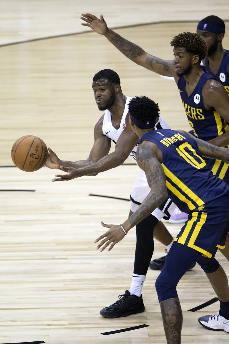 Portland Trail Blazers guard Emmanuel Mobiay (58) passes flanked by Indiana Pacers forward Devi ...