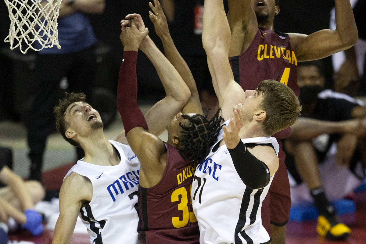 Cleveland Cavaliers forward Evan Mobley (4) and guard Isaac Okoro (35) jump to block a shot by ...