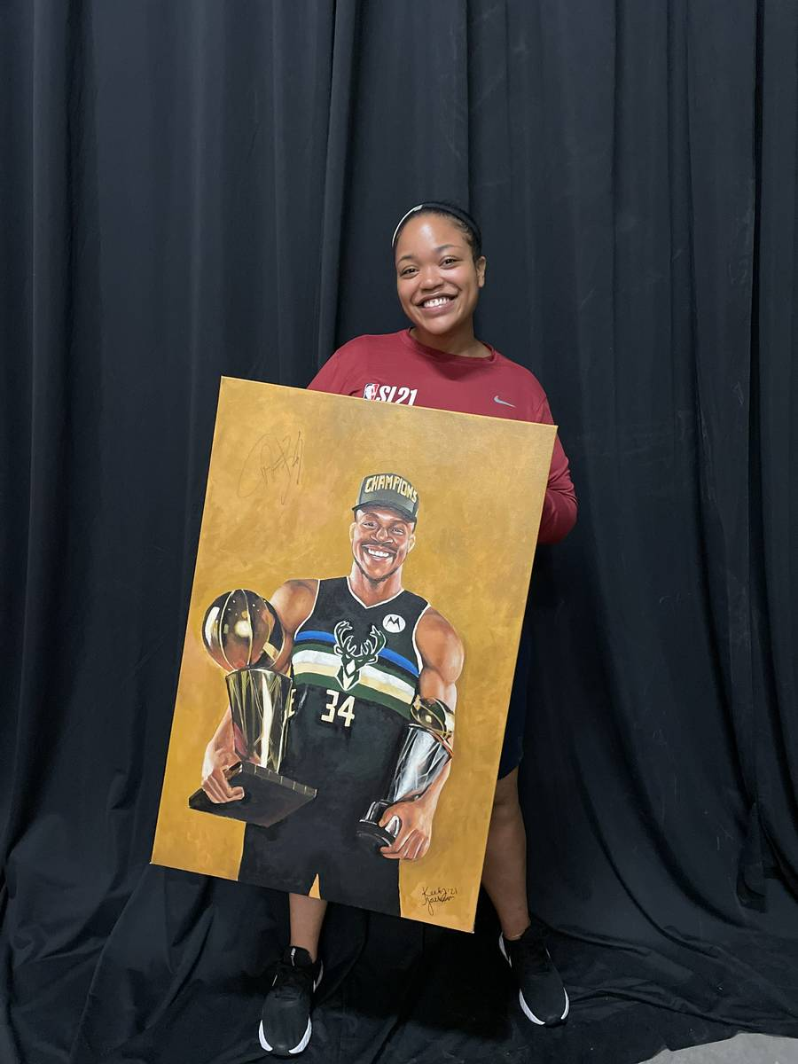 Keely Jackson poses for a photo with her portrait of Milwaukee Bucks forward and reigning NBA F ...