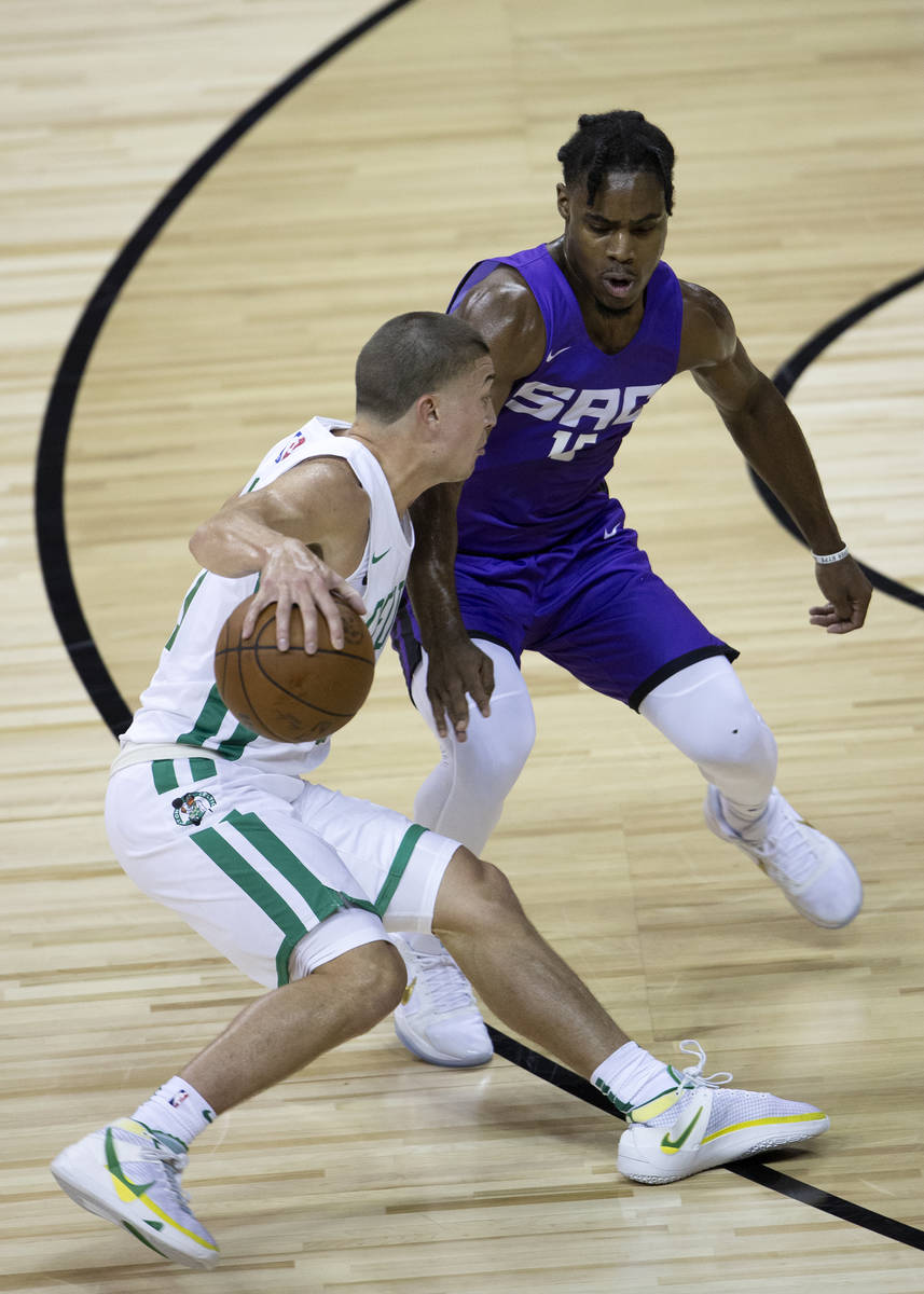 Boston Celtics guard Payton Pritchard (11) dribbles around Sacramento Kings guard Davion Mitche ...