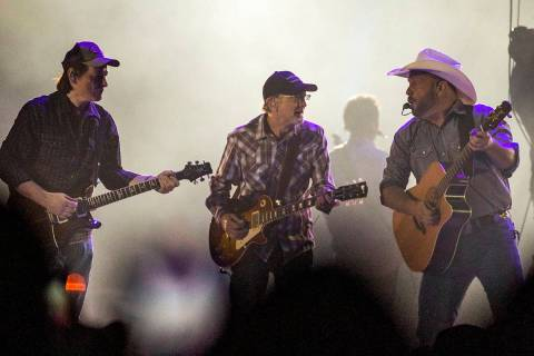 Garth Brooks performs with his band mates before the crowd at Allegiant Stadium on Friday, July ...