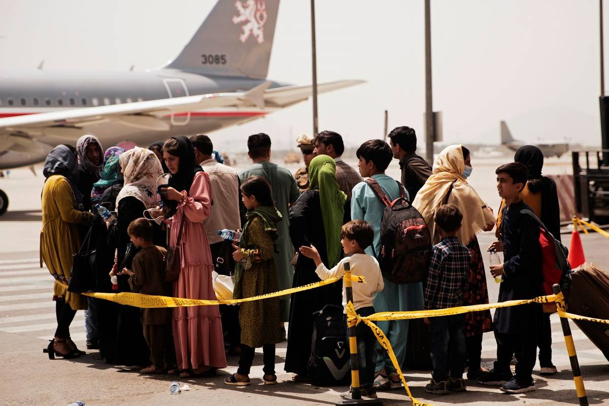 Civilians prepare to board a plane during an evacuation at Hamid Karzai International Airport, ...