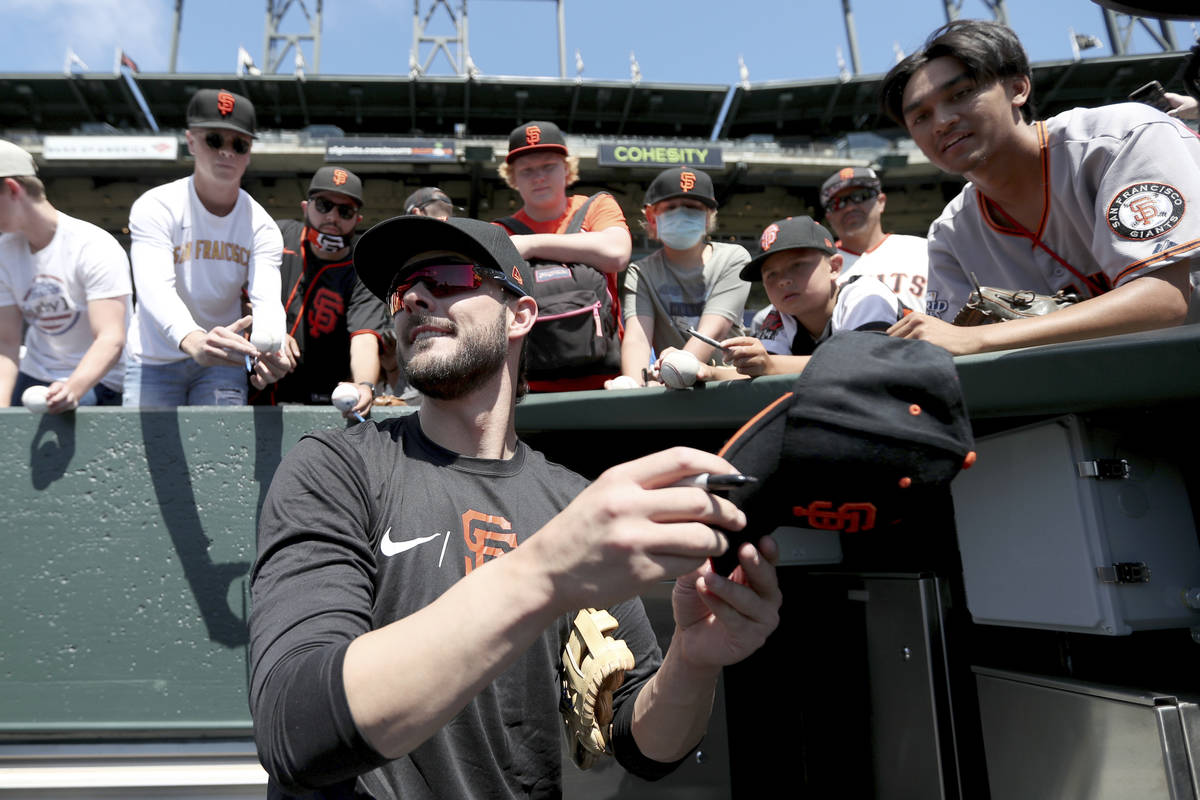 San Francisco Giants' Kris Bryant gives autographs to fans prior to a baseball game against the ...