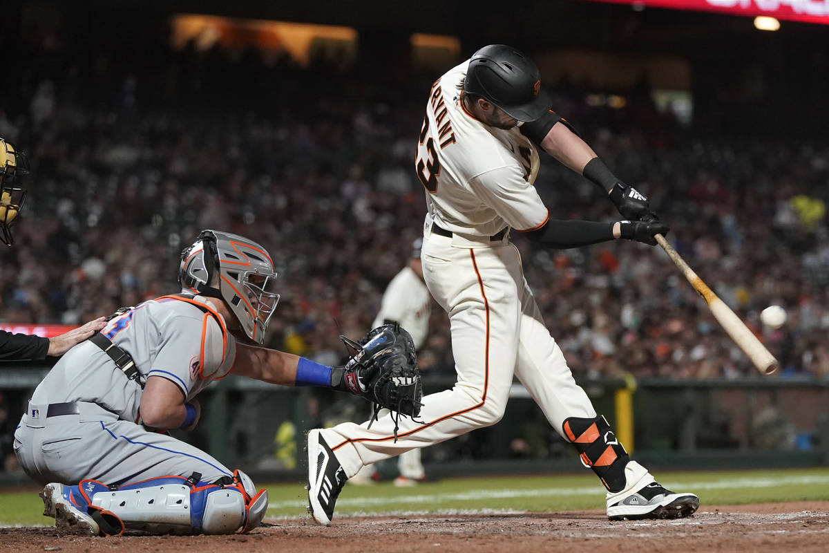 San Francisco Giants' Kris Bryant, right, hits a two-run home run in front of New York Mets cat ...