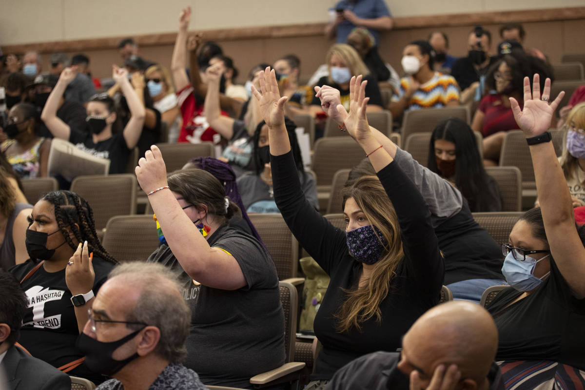People raise their hands to show support for a speaker's comments during a Clark County School ...