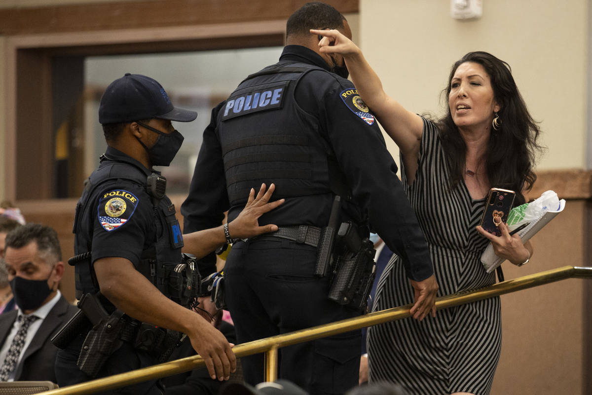 A woman is escorted out of a Clark County School District Board of Trustees meeting where an up ...