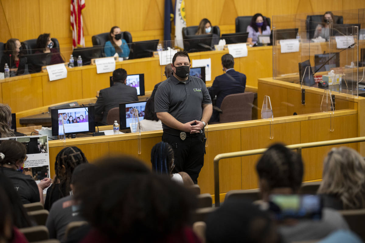 A security guard watch over a Clark County School District Board of Trustees meeting at the Cla ...