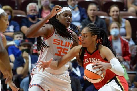 Las Vegas Aces' Aja Wilson (22) drives to the basket against Connecticut Sun's Jonquel Jones (3 ...