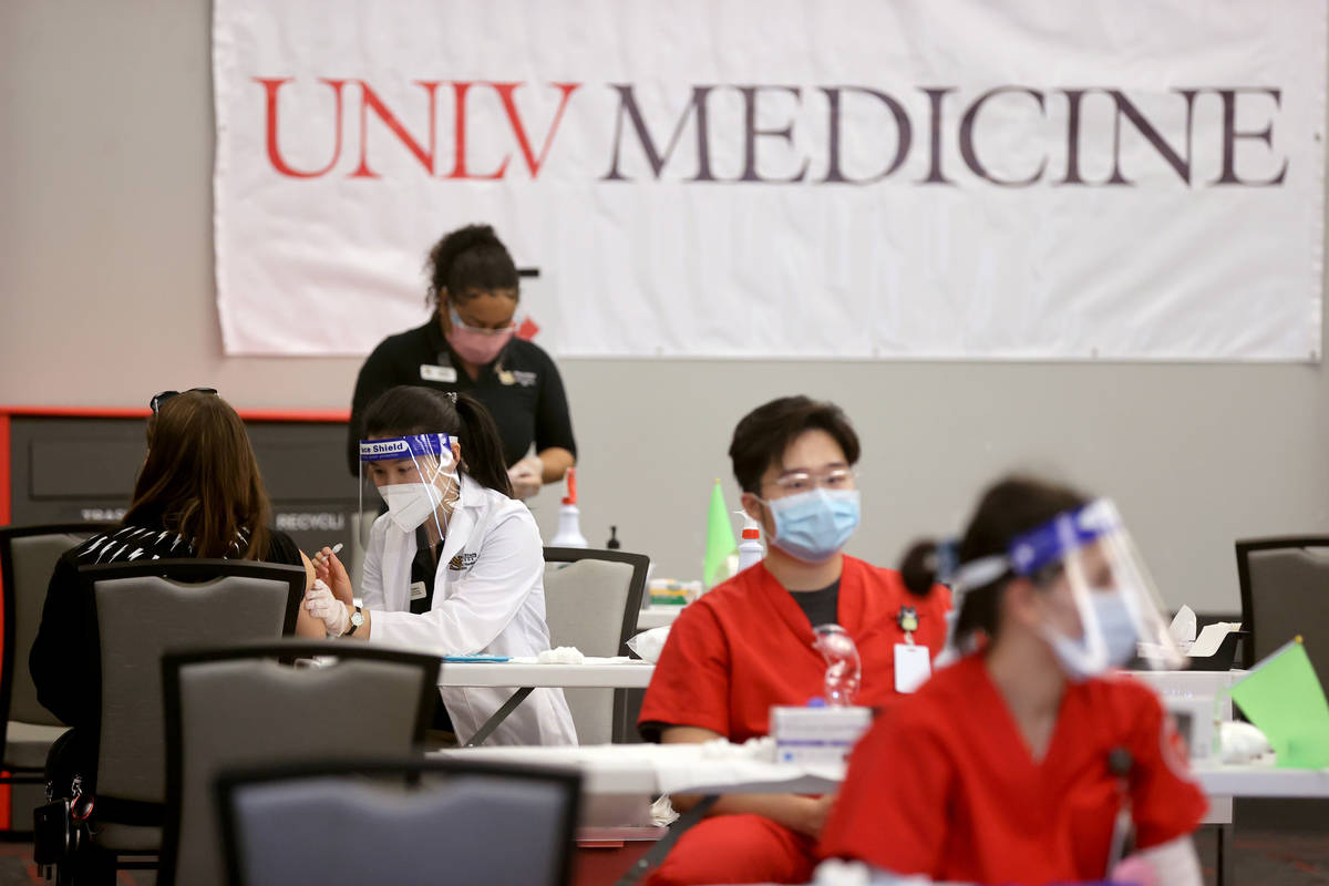 Angela Kong, left, a Nevada State College nursing student, gives a COVID-19 vaccine during a UN ...