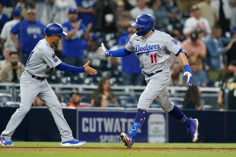 Los Angeles Dodgers' AJ Pollock, right, reacts with third base coach Dino Ebel after hitting a ...