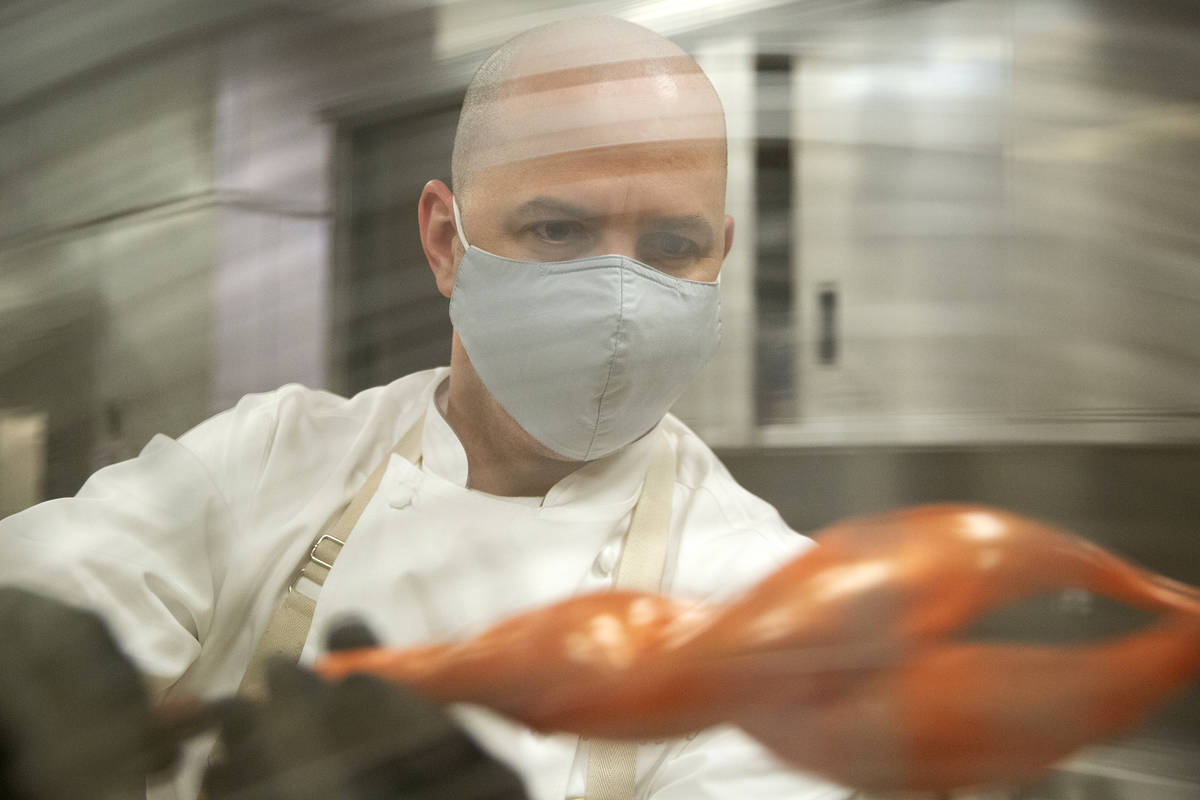 Executive pastry chef Mathieu Lavallee cools a blown sugar flame that will adorn the Raiders to ...