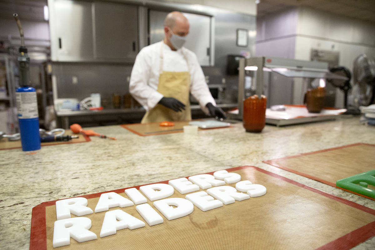 Executive pastry chef Mathieu Lavallee works in the background as Raiders lettering made of sug ...