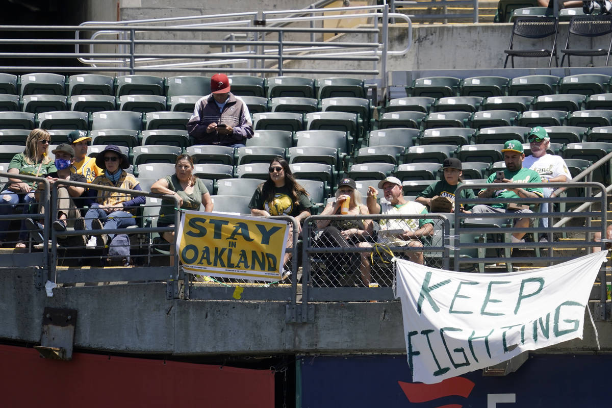Fans sit behind a sign that reads Stay in Oakland during the first inning of a baseball game be ...