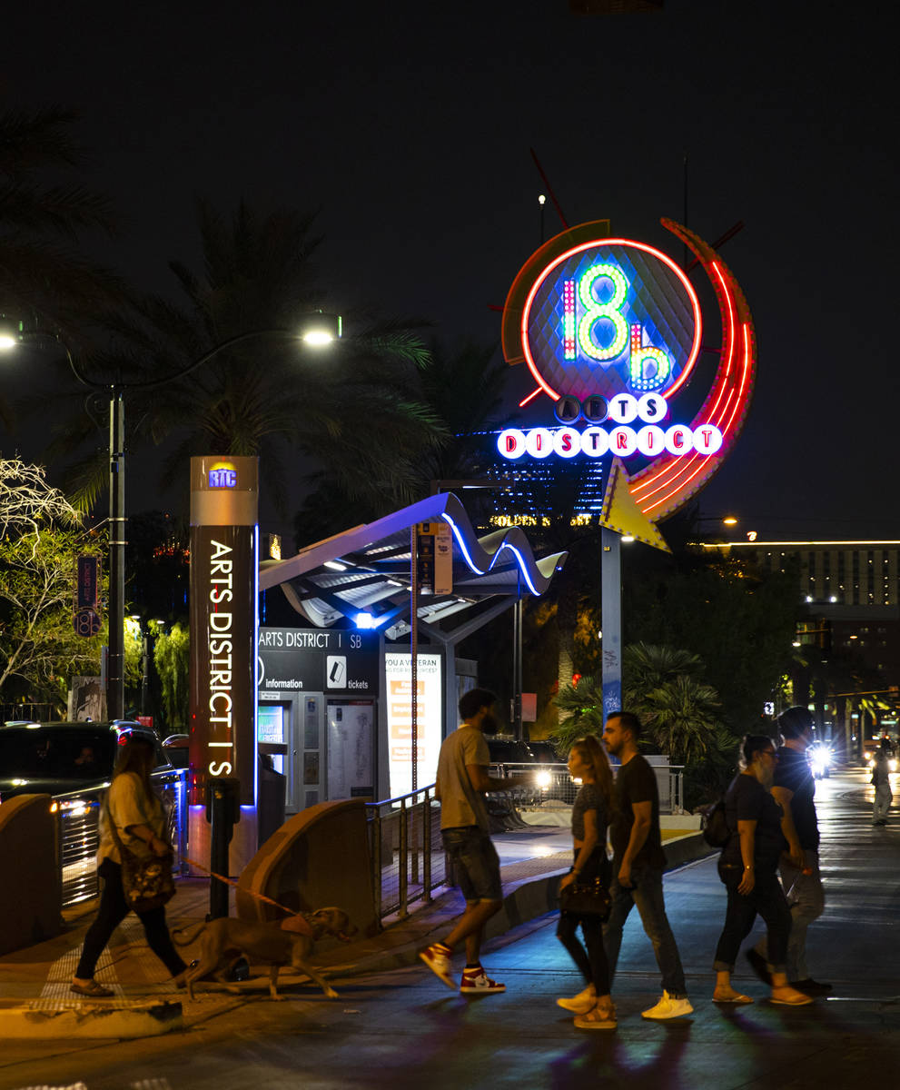 People cross the street near the 18B Arts District neon sign during First Friday in downtown La ...