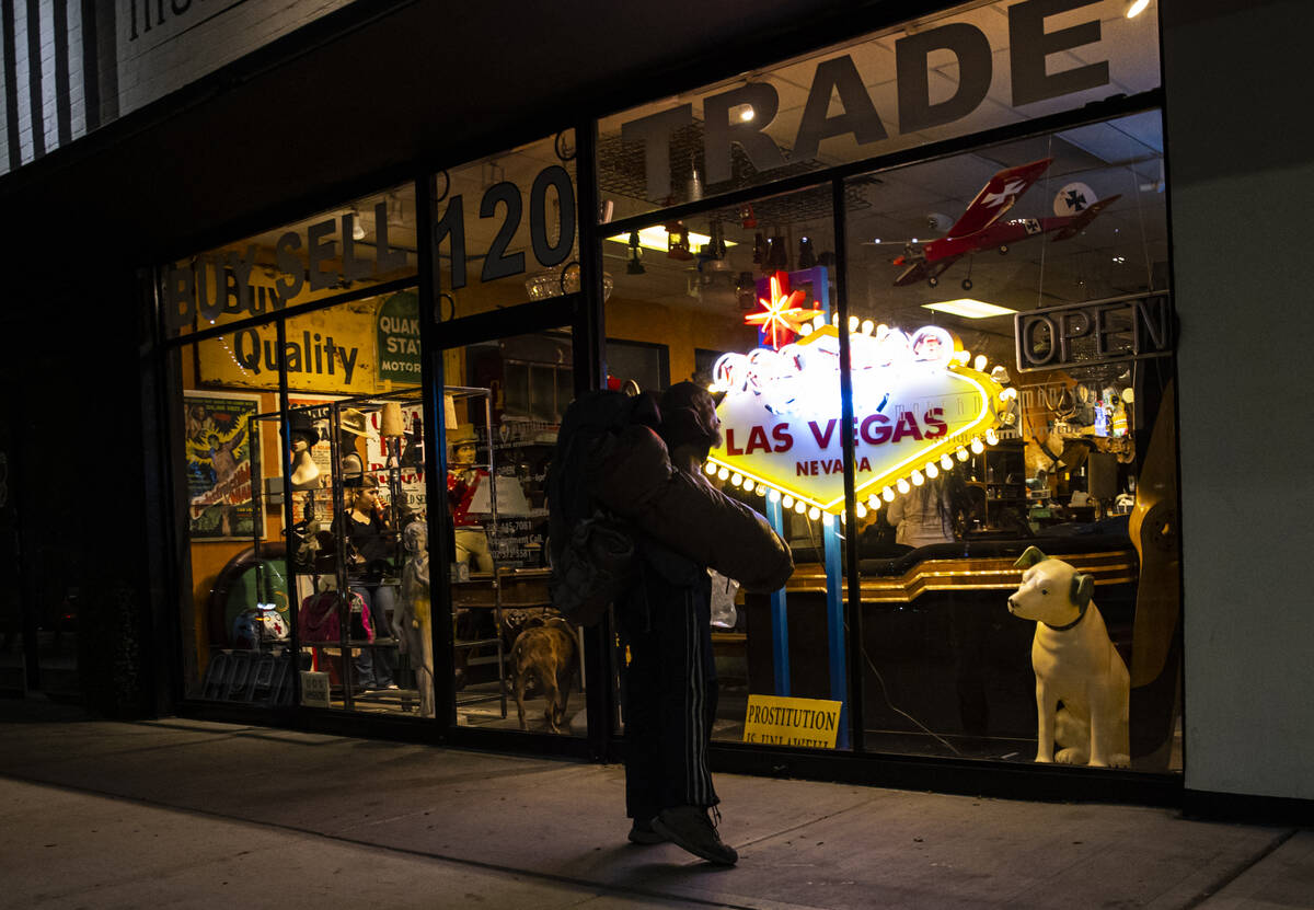 A passerby looks into Modern Mantiques on Main Street during First Friday in the Arts District ...