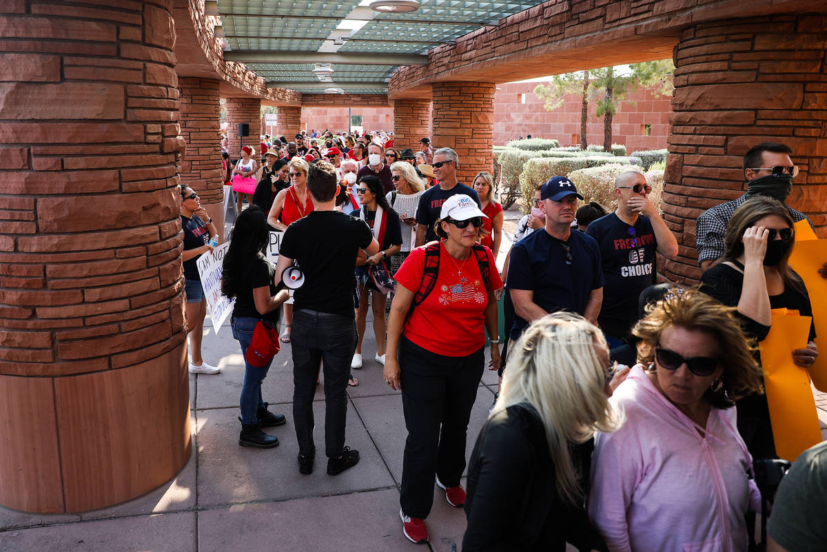 Concerned citizens wait in line for a Clark County School Board meeting regarding the possible ...
