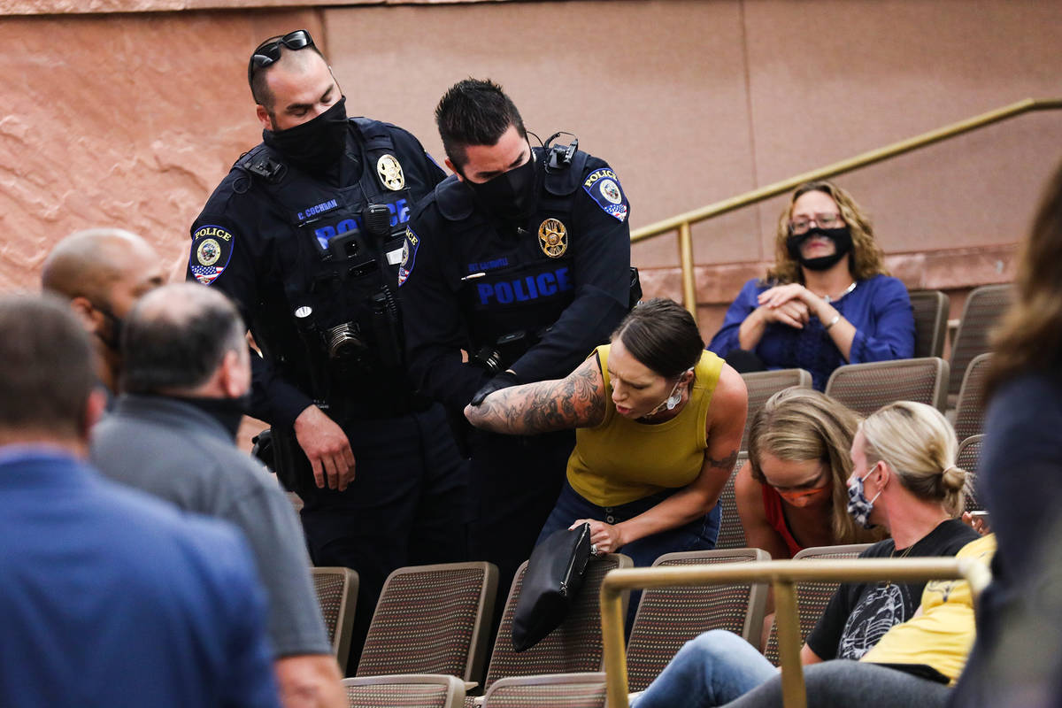 A woman is escorted out by police after disrupting a Clark County School Board meeting regardin ...