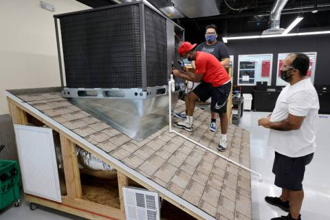 Students, from left, Brandon Dickerson, Kevin Navarro and Eric Ramos work on a rooftop air cond ...