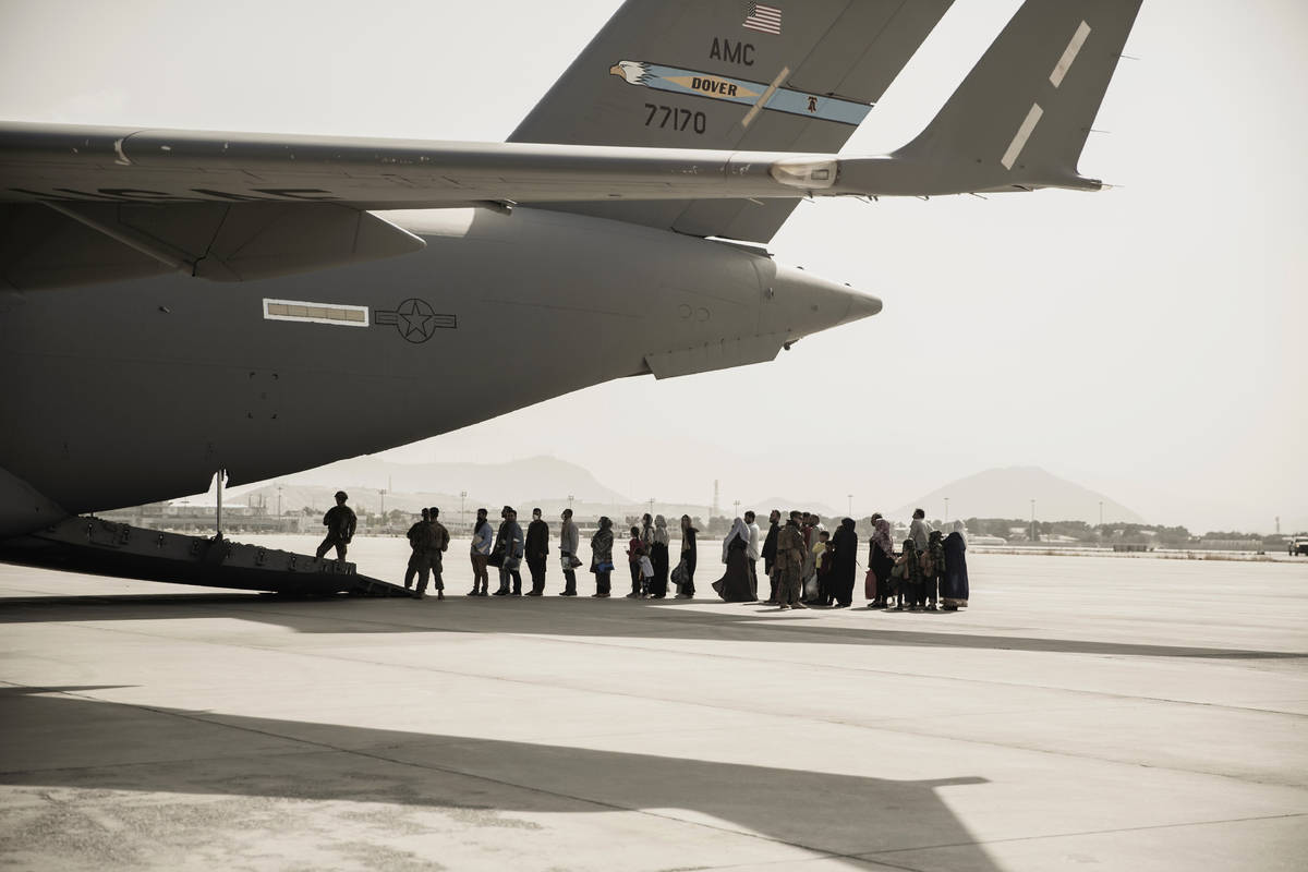 In this image provided by the U.S. Marine Corps, evacuees wait to board a Boeing C-17 Globemast ...