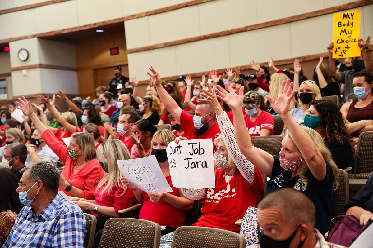Concerned members of the public raise their hands in approval of a person's public comme ...