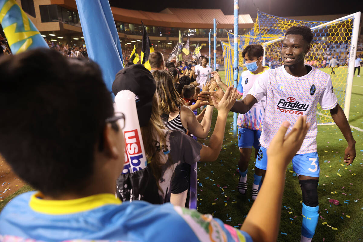 Las Vegas Lights Mohamed Traore high fives fans at the end of an USL Championship soccer game a ...