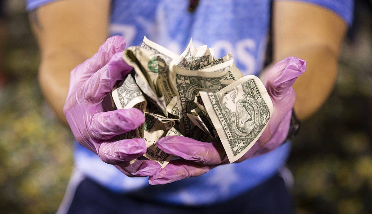"""Fans show off the money they won during the annual """"$5,000 Cash Drop presented by Jarrit ..."""