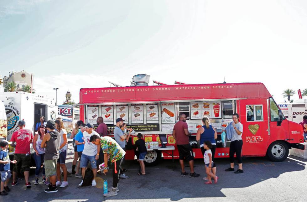 Individuals wait to receive their waffles from WAFL Truck during the Great American Foodie Fest ...