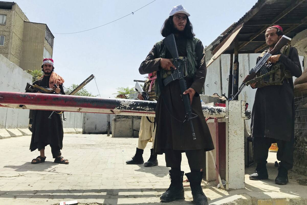 Taliban fighters stand guard at a checkpoint near the US embassy that was previously manned by ...