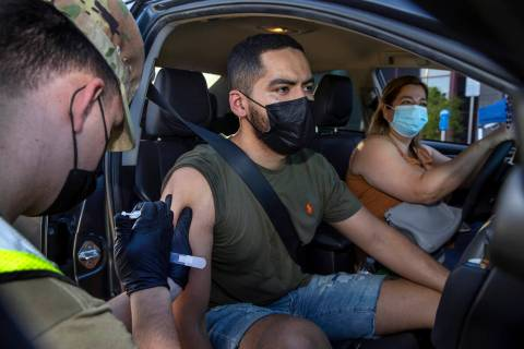 (From left) Nevada National Guard SPC Austin Czarnecki gives a COVID-19 vaccination to Luis Ger ...