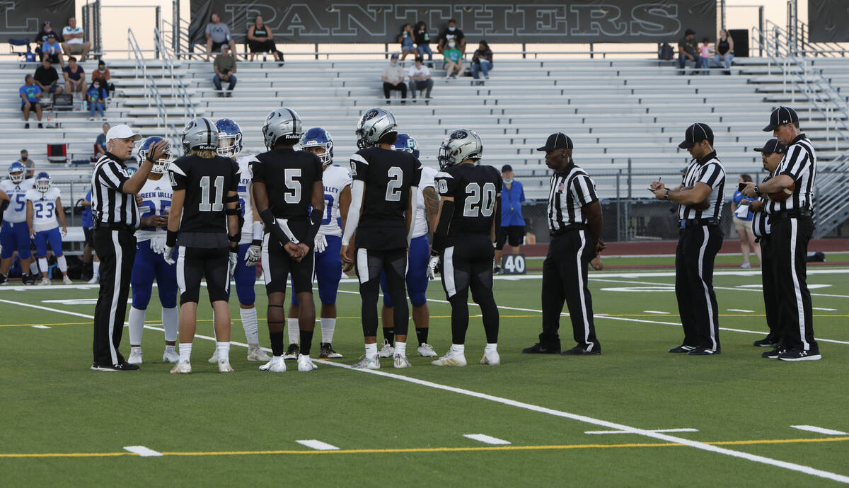 Referee Shane Lewis, left, white cap, talks to players during the coin toss before a football g ...