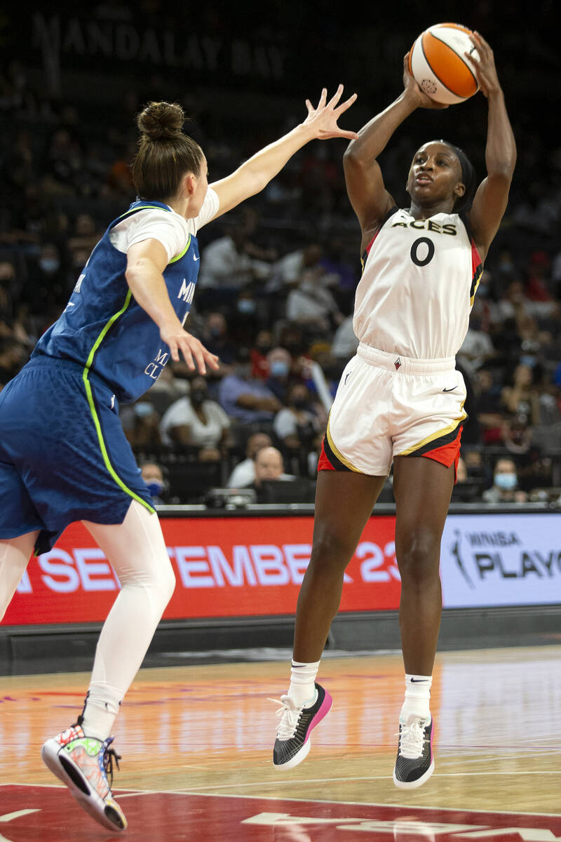Las Vegas Aces guard Jackie Young (0) shoots a three-pointer guarded by Minnesota Lynx forward ...