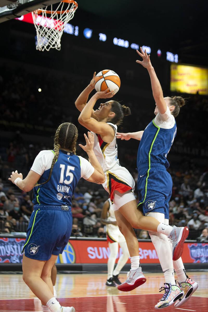 Las Vegas Aces guard Kelsey Plum (10) jumps for a layup flanked by Minnesota Lynx guard Rachel ...