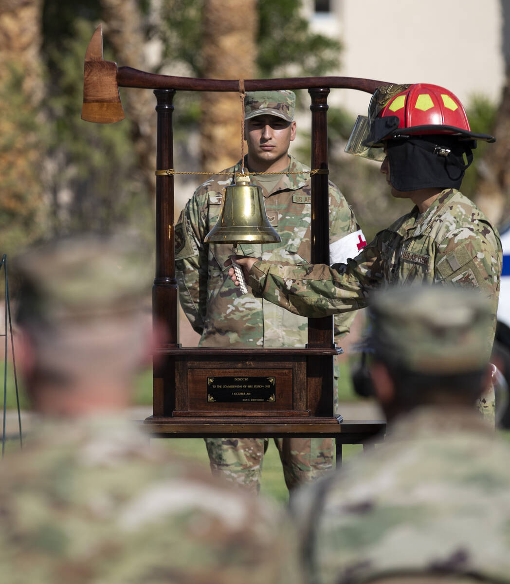 Military members ring a bell dedicated to Fire Station One during the Nellis Fire and Emergency ...