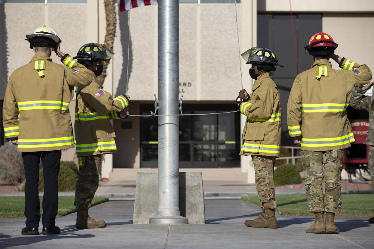 Firefighters lower the American Flag to half-staff during the Nellis Fire and Emergency Service ...