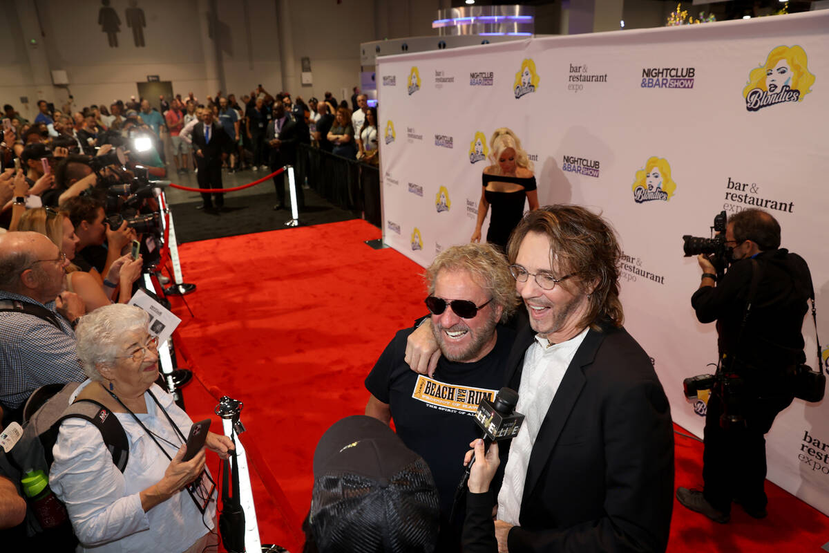 Sammy Hagar, left, and Rick Springfield walk the red carpet as Jenny McCarthy, rear, poses for ...